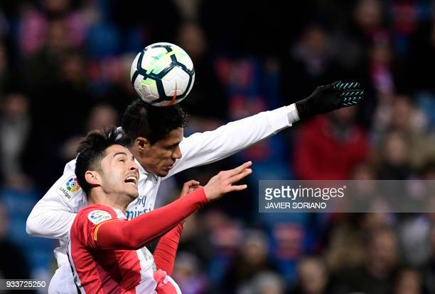 Girona's Spanish defender Juanpe Ramirez vies with Real Madrid's French defender Raphael Varane during the Spanish League football match between Real...