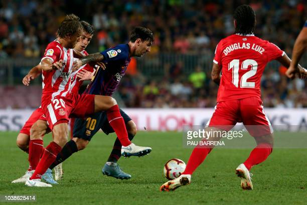 Girona's Spanish defender Marc Muniesa and Girona's Spanish midfielder Alex Granell vie with Barcelona's Argentinian forward Lionel Messi during the...