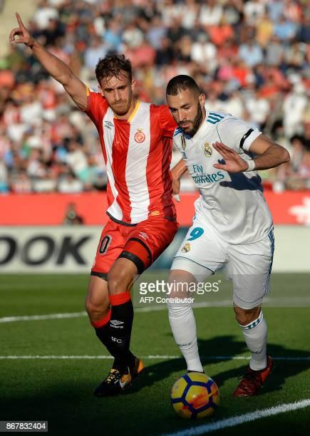 Girona's Spanish defender Marc Muniesa vies with Real Madrid's French forward Karim Benzema during the Spanish league football match Girona FC vs...