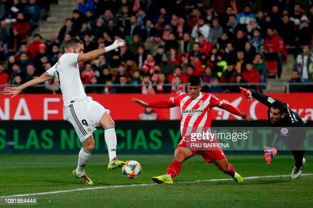 Girona's Spanish goalkeeper Gorka Iraizoz and Girona's Spanish midfielder Borja Garcia stop a shot on goal by Real Madrid's French forward Karim...