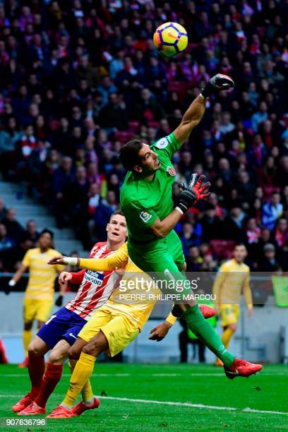 Girona's Spanish goalkeeper Gorka Iraizoz punches the ball away next to Atletico Madrid's French forward Kevin Gameiro during the Spanish league...