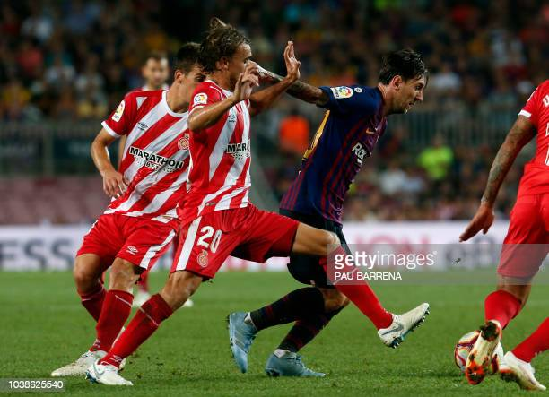 Girona's Spanish midfielder Alex Granell and Girona's Spanish defender Marc Muniesa vie with Barcelona's Argentinian forward Lionel Messi during the...