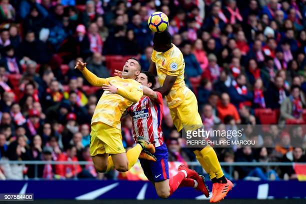 Girona's Spanish midfielder Borja Garcia and Girona's Kenyan forward Michael Olunga head the ball with Atletico Madrid's Croatian defender Sime...