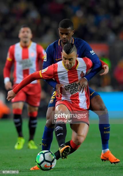 Girona's Spanish midfielder Borja Garcia vies with Barcelona's Portuguese defender Nelson Semedo during the Spanish league football match between FC...