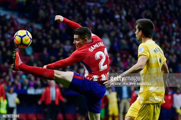 Girona's Spanish midfielder Pere Pons challenges Atletico Madrid's French forward Kevin Gameiro during the Spanish league football match between Club...