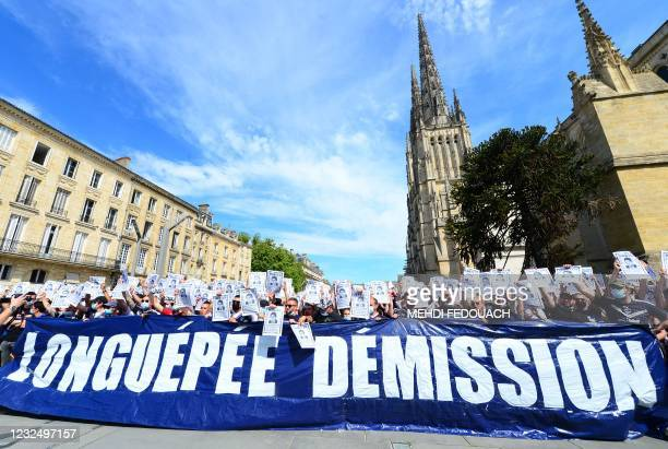 """Girondins de Bordeaux' supporters of the """"Ultramarines"""" group hold flares and a banner reading """"Longuepee resign"""" as they gather on Pey-Berland..."""