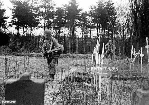 GIs Fred Praily and Robert Svenson of K company 331st Regiment 2nd Battalion of the 83rd Infantry Division pass by graves during fighting as part of...