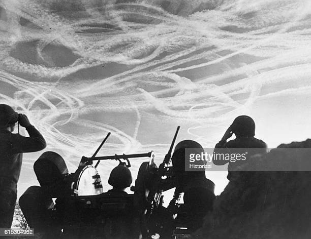 GIs of the M51 Antiaircraft Battery are silhouetted against a sky streaked with vapor trails from Allied and enemy planes engaged in a Christmas Day...