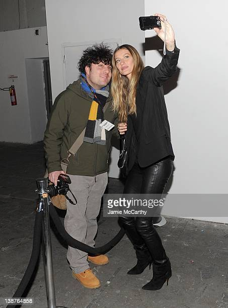 Gisele Bundchen poses with a fan backstage at the Alexander Wang Fall 2012 fashion show during MercedesBenz Fashion Week at the Pier 94 on February...