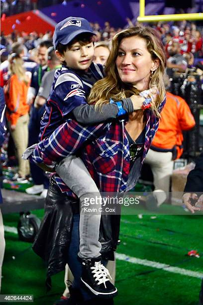 Gisele Bundchen wife of Tom Brady of the New England Patriots walks on the field with their son Benjamin after defeating the Seattle Seahawks during...