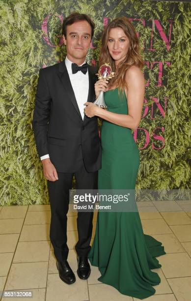 Gisele Bundchen winner of The Vogue Eco Laureate Award poses with presenter Emanuele Farneti backstage at The Green Carpet Fashion Awards Italia at...