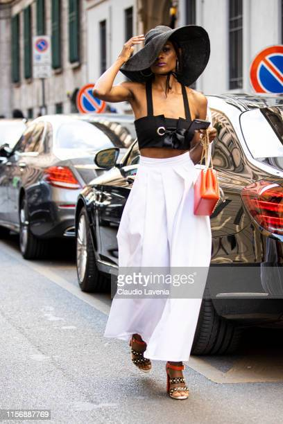 Gisele De Assis wearing a black crop top white wide leg pants black and orange decorated heels orange bag and big black straw hat is seen outside...