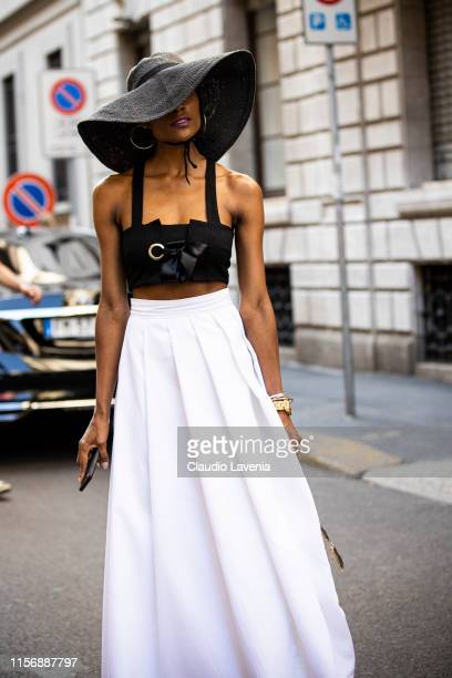 Gisele De Assis wearing a black crop top white wide leg pants orange bag and big black straw hat is seen outside Giorgio Armani show during the Milan...