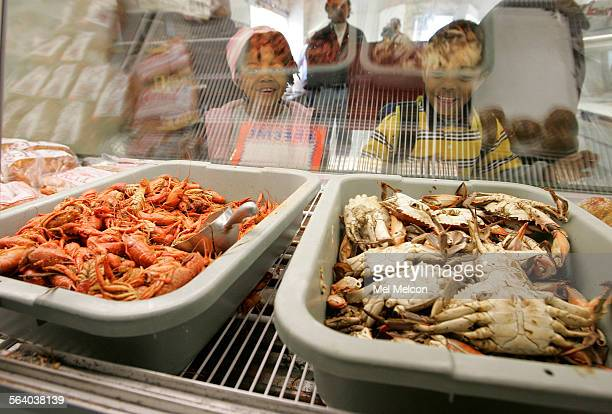 Gisele Flowers and her brother Richard Boudroux 5 look at cooked crawfish and blue crabs on display inside the New Orleans Fish Market on Vernon Ave...