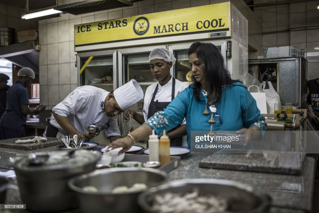 Gita Jivan, owner of Geet Restaurant (R) speaks to head Chef Kamal Singh (L) and other members of the kitchen staff work in the restaurant on February 20, 2018 in Pretoria. The restaurant is the choice caterer for the Indian cricket team during their visits to play in South Africa. /