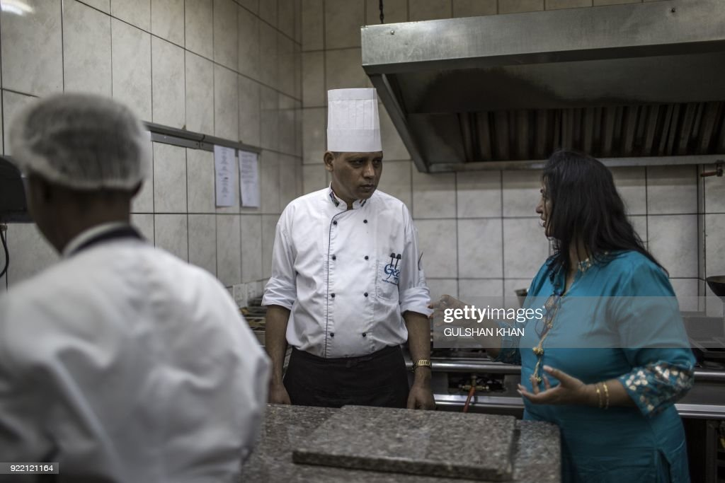 Gita Jivan, owner of the Geet Restaurant (R) speaks to head Chef Kamal Singh (C) in the kitchen at the restaurant premises in Pretoria on February 20, 2018. The restaurant is the choice caterer for the Indian cricket team during their visits to play in South Africa. /