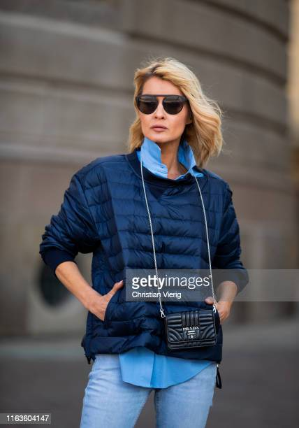 Gitta Banko is seen wearing a blue down sweater by Holubar a blue blouse by Steffen Schraut light blue jeans by Closed black Prada micro bag and a...