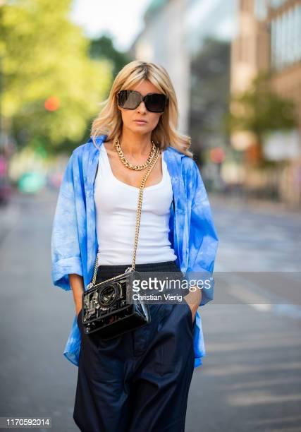 Gitta Banko is seen wearing a dark blue Ali double-waist wide-leg pants from Tre by Natalie Ratabesi, white ripped tanktop by Zara, a blue tie dye...