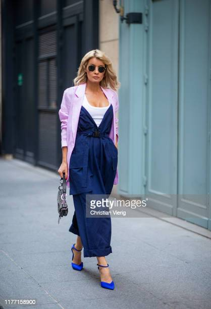 Gitta Banko is seen wearing a dark blue overall by Maison Margiela a white tank top by Zara an oversized rosé linen blazer by Boscana a Dior Oblique...