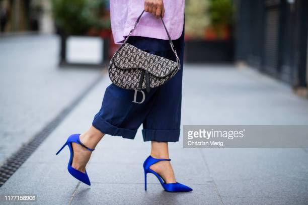 Gitta Banko is seen wearing a dark blue overall by Maison Margiela, a white tank top by Zara, an oversized rosé linen blazer by Boscana, a Dior...