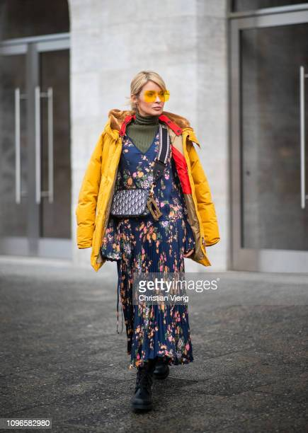 Gitta Banko is seen wearing a floral patterned dress with pleated skirt by Steffen Schraut over an olive green turtleneck sweater from Zara yellow...