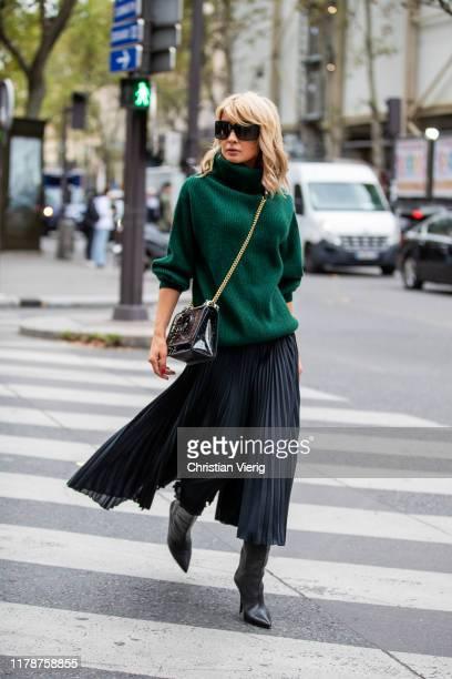 Gitta Banko is seen wearing a green oversized cashmere turtleneck sweater, a black pleated silk skirt- pants by Boscana, black boots by Yeezy, a...