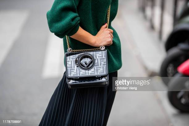 Gitta Banko is seen wearing a green oversized cashmere turtleneck sweater a black pleated silk skirt pants by Boscana a black Kan I F bag by Fendi...