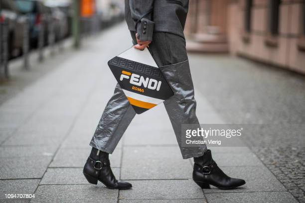 Gitta Banko is seen wearing a grey asymmetrical blazer and trousers by Balossa, Fendi x Fila leather clutch with wrist strap, black cowboy boots by...