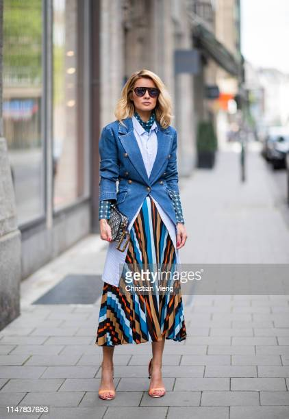 Gitta Banko is seen wearing a layering look containing a blue transparent turtleneck top with white dots long oversize striped blouse and a...