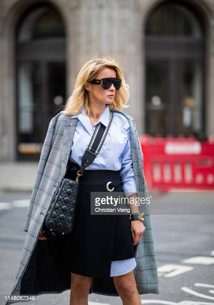 Gitta Banko is seen wearing a layering look containing a long oversize striped blouse a grey checked oversize coat by Steffen Schraut black lambskin...