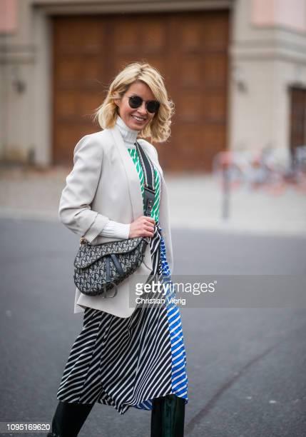 Gitta Banko is seen wearing a multicolored striped dress and blazer by Steffen Schraut tubularshaped green metallic overknee boots by Alexandre...
