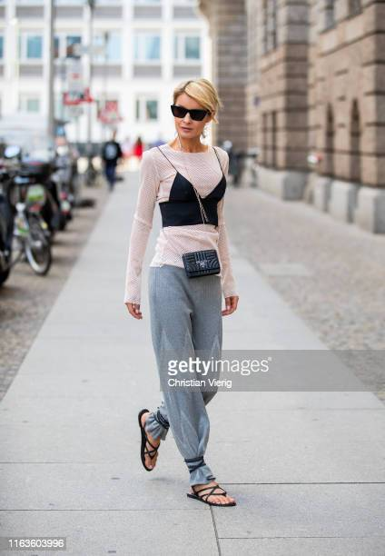 Gitta Banko is seen wearing a powdercolored stretch sweater and grey cashmeresilk pants by Boscana a black silk triangle bra by Alexander Wang a...