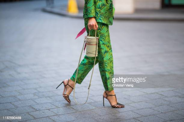 Gitta Banko is seen wearing a twopiece taffeta suit in the color Greenery with palm branch print by Dawid Tomaszewski black shirt from Zara statement...