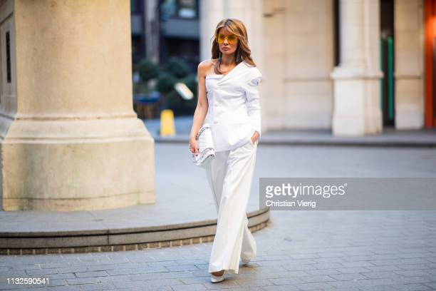 Gitta Banko is seen wearing a white oneshoulder blazer by Pearl and Rubies white Marlene pants with pleated waistband by Glamoda white Chanel bag...