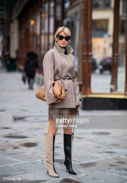 Gitta Banko is seen wearing beige feather skirt, blazer by Tere Sha, two tone boots by Gestuz, sunglasses by Mykita x Maison Margiela, brown bag and...