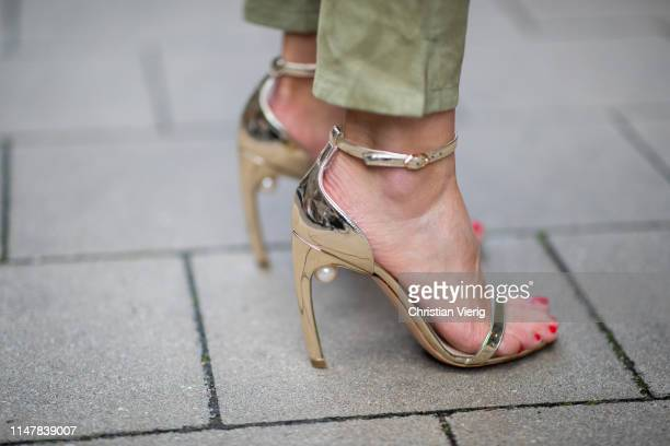 Gitta Banko is seen wearing golden ankle-strap sandals with signature pearl embellishment at the junction of the heel and sole by Nicholas Kirkwood...