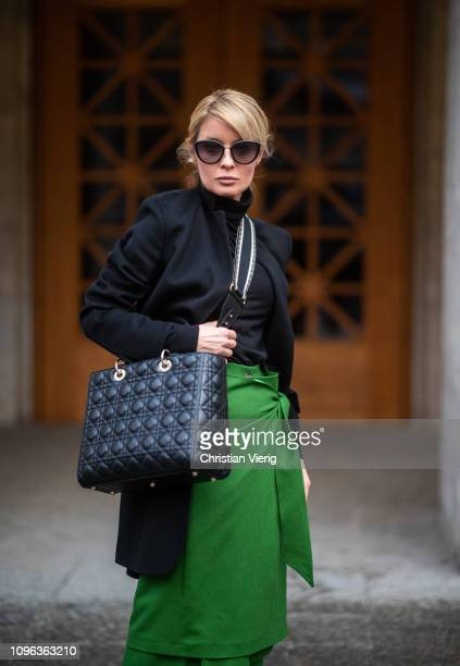 Gitta Banko is seen wearing green cashmere skirt over green cashmere trousers by Manufaktur Boscana black cashmere turtleneck sweater and black coat...