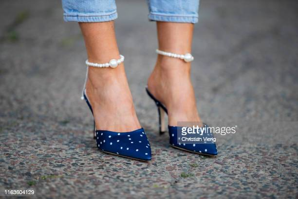 Gitta Banko is seen wearing navy and white polka dotted satin mules included ankle bracelets finished with pearlescent by Magda Butrym on July 22...