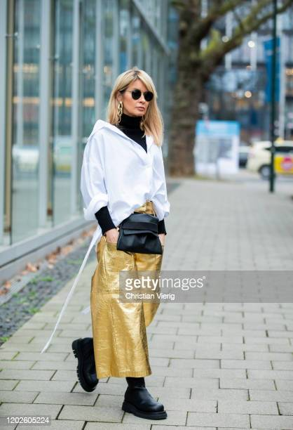 Gitta Banko is seen wearing white oversized blouse, black ribbed turtleneck sweater, gold leather culotte and black leather belt bag all Boscana x...