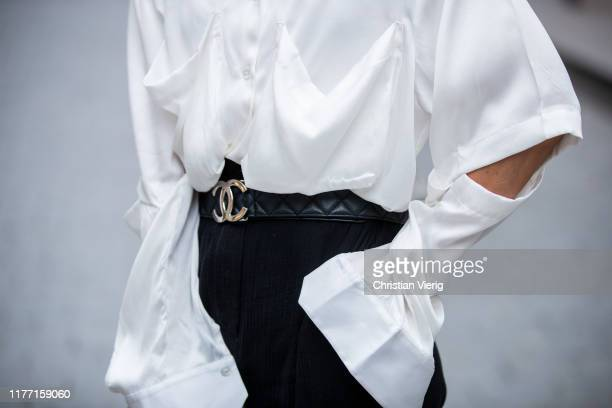 Gitta Banko is seen wearing white silk blouse with cut-out details by Balossa, black high waist pants by Nanushka, black quilted belt by Chanel...