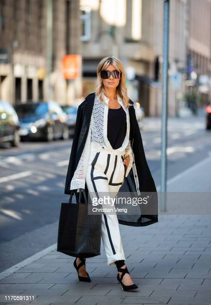 Gitta Banko is seen wearing white trousers with graphic pattern, a black coat and black tanktop by Anette Goertz, white laced blouse, black pumps...