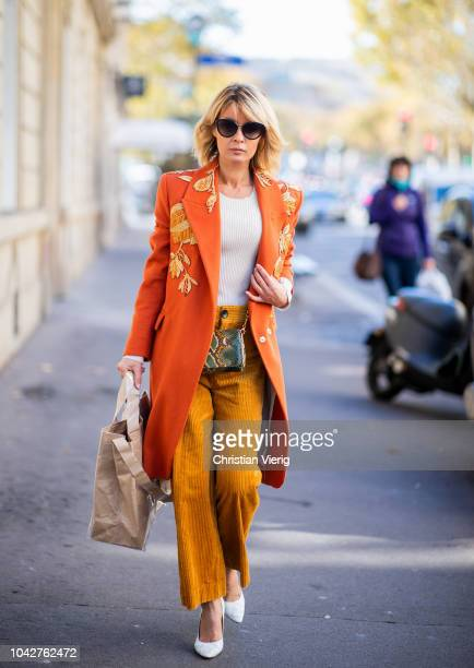 Gitta Banko wearing a beige sweater by Steffen Schraut orange colored coat with gold embroidery by Dawid Tomaszewski camel cord pants by Zara...
