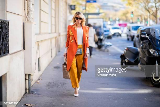 Gitta Banko wearing a beige sweater by Steffen Schraut orange colored coat with gold embroidery by Dawid Tomaszewski camel cord pants by Zara...