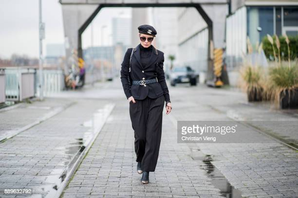 Gitta Banko wearing a black blazer with brooch and black culottes trousers by AirField a black turtleneck sweater by Bruno Manetti glove with golden...