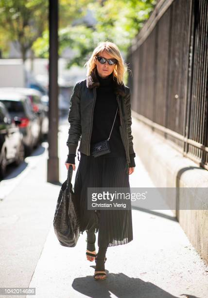 Gitta Banko wearing a black cashmere sweater and black pleated skirt by Boscana green bomber jacket by Steffen Schraut a black micro bag and black...
