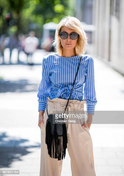 Gitta Banko wearing a blue and white striped blouse with frontknot detail and beigecolored flared trousers by GR8FUL black mini fringed leather bag...