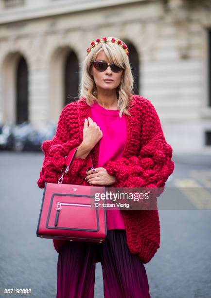 Gitta Banko wearing a chunky knitted Warm Up Ruby cardigan by Mums Handmade pink cashmere sweater by Jadicted pleated viscose trousers in purple to...