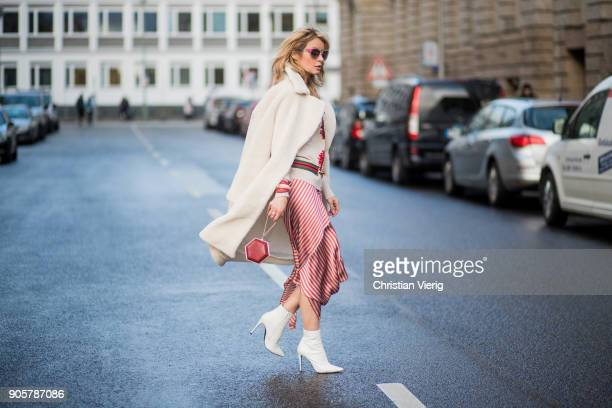 Gitta Banko wearing a creamcolored teddy bear coat by Stand creamcolored cardigan by Steffen Schraut asymmetrical skirt with knot details from Top...
