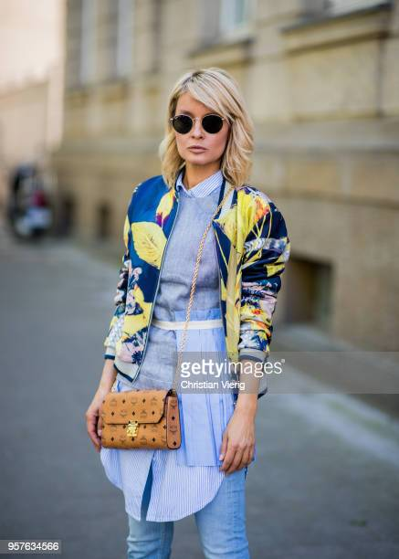 Gitta Banko wearing a floral patterned Bomber jacket by AirField striped oversize blouse by Joseph top with asymmetrical pleated cloth by Erika...
