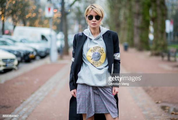 Gitta Banko wearing a grey oversize hoodie with hand painted print by Wodka Ogurez a grey checked cotton skirt by Isabel Marant black woolblend and...